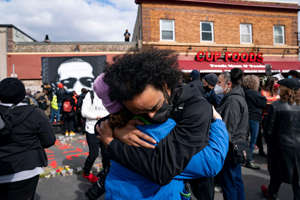 a group of people standing in front of a building: Nic Hernandez and Emma Ruddock hug in celebration after hearing the verdict of Derek Chauvin at George Floyd Square on April 20, 2021.