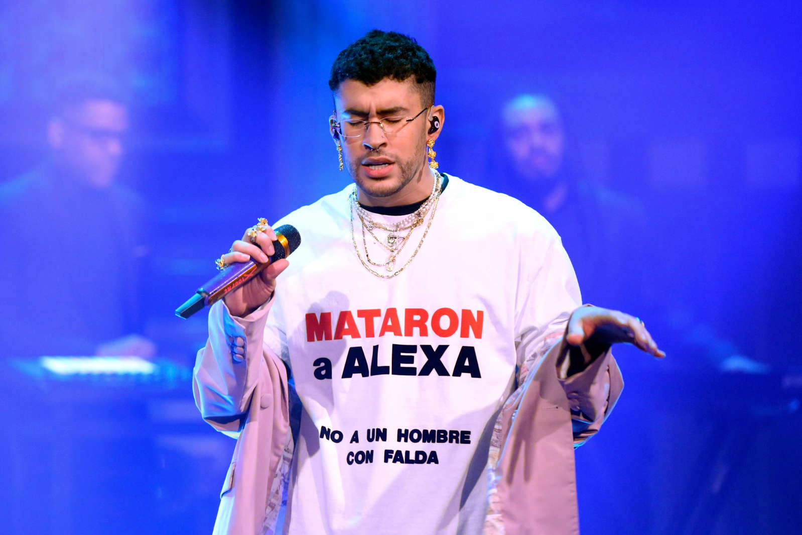 a baseball player holding a bat while standing on a stage: Rapper Bad Bunny performs on The Tonight Show Starring Jimmy Fallon on February 27, 2020. He wore a shirt bringing attention to the death of Alexa Negrón Luciano, a Puerto Rican trans woman who was killed while using a women's bathroom. Andrew Lipovsky/NBC/NBCU Photo Bank via Getty Images