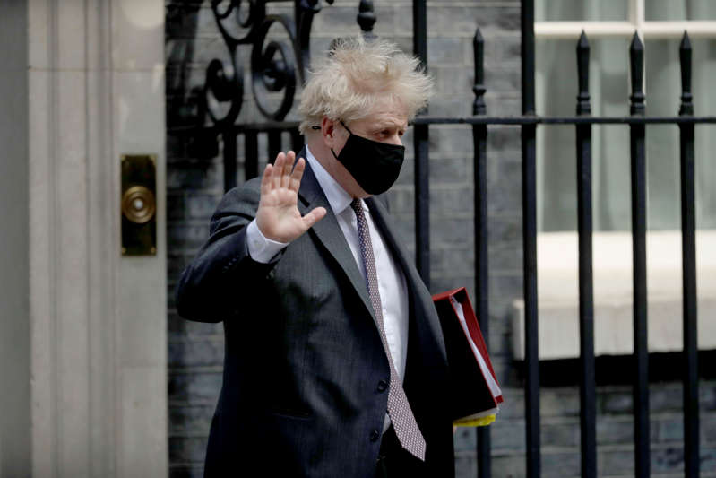 British Prime Minister Boris Johnson waves at the media as he leaves 10 Downing Street in London, to attend the weekly Prime Minister's Questions at the Houses of Parliament, in London, Wednesday, April 21, 2021. (AP Photo/Matt Dunham)