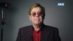 Elton John wearing glasses and looking at the camera: Elton John and Michael Caine take part in NHS campaign