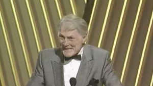 Jack Palance in a suit standing in front of a fence: Jack Palance winning an Oscar® - Best Supporting Actor, City Slickers - 64th Annual Academy Awards®.