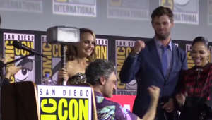 a man holding a sign: Marvel announces Natalie Portman to play female Thor