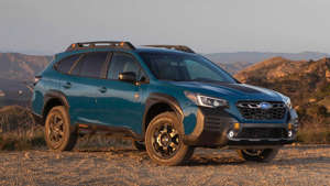 a blue car on a dirt road: 2022 Subaru Outback Wilderness Edition