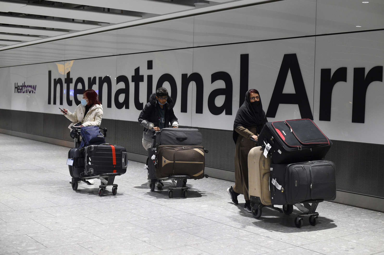 Passengers push luggage through the Arrival Hall of Terminal 5 at London's Heathrow Airport after arriving into the UK following the suspension of the travel corridors. Passengers arriving from anywhere outside the UK, Ireland, the Channel Islands or the Isle of Man must have proof of a negative coronavirus test and self-isolate for 10 days. Picture date: Monday January 18, 2021. (Photo by Kirsty O'Connor/PA Images via Getty Images)
