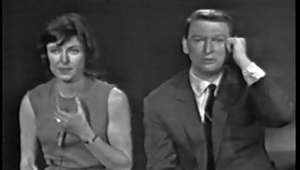 "a group of people posing for a photo: Mike Nichols and Elaine May perform their routine about a frustrated man in a telephone booth ""interacting"" with a Bell Telephone Information operator and her management.  For those whose only experience with a telephone is a cell phone; in days gone by, thousands of coin-operated phone booths (""pay stations"" in telephone company jargon) were available in conspicuous places for the public to make local and long-distance telephone calls while away from home.  Generally, each booth or station had a telephone directory within reach so that a caller could look up the number of the person he/she was trying to reach on a local call.  Sometimes these directories (""telephone books"" in the vernacular) would disappear from their assigned locations.  Such is the case with this caller (Nichols).  He, instead drops a dime in the 10-cent slot and dials the Information Operator.  So long as he is talking with the Information Operator, his dime is held in the phone but not actually collected.  Normally, the coin would be returned once the call to the Information Operator is terminated.  The dime (for decades before, only a nickel would have been required) comes out of a slot and back to the caller.  Somehow, this caller's dime gets deposited before his session with the operator ended; and, he has no more dimes with him.  The audio for this post was recorded on my reel-to-reel tape recorder on July 9, 1965 from Jack Paar's Friday night program on NBC-TV.  (Home video recorders were another ten years away.)  This broadcast was a summer re-run--the original having been aired during the regular broadcast season.  The video in this post is a kinescope recording taken from a special program called ""Jack Paar is Alive and Well"", aired December 19, 1987.  The audio on that program, as is the case with many kinescopes (which were filmed from a TV monitor) is inferior to what was originally broadcast over the air.   I synchronized the separate video and audio (not perfectly, but ""close enough for telephone work"", as some of us used to say in the company).  By the way,  on the original telecast, Jack Paar, in his introduction of the duo, indicated that, out of all of their many routines, he had asked them to perform this particular routine.  He then went on to say, ""Here then--two people who have more talent than you could shake a wand at.""  Also in the original telecast, at the end of the routine, the audience's applause lasted fifteen full seconds before it was abruptly faded out as the program cut to a commercial."