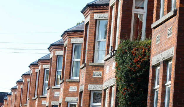 a tall brick building: A single mother, who had to speak from her car away from the ears of her children, said she was thinking of making the difficult decision of moving to Donegal as she can't afford Dublin rental prices. Pic: Leah Farrell / RollingNews.ie