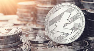 a clock on a table: Image of one litecoin in front of many stacks of litecoins