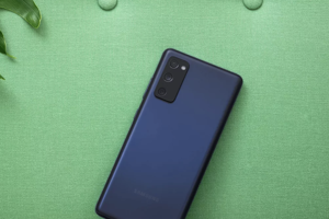 a cellphone lying on a green blanket: samsung-galaxy-s20-fe-review-colors-best-phone.png