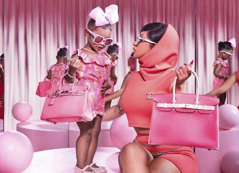 a person sitting on a chair in front of a curtain: Cardi B and her daughter hold designer handbags