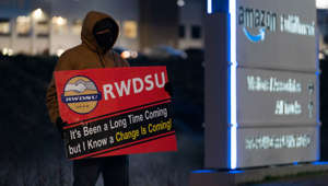 a sign on the side of a building: An RWDSU union rep holds a sign outside the Amazon fulfillment warehouse at the center of a unionization drive on March 29, 2021 in Bessemer, Alabama.