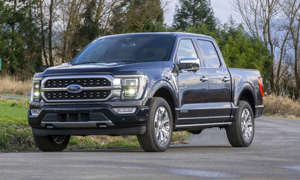a car parked on the side of a road:          All new for the 2021 model year, the Ford F-150 offers a wide range of innovations — the most interesting being the first hybrid powertrain for the popular truck line. And this new hybrid delivers more than mere fuel efficiency — an onboard power generator in the 2021 Ford F-150 PowerBoost Hybrid brings a whole new level of utility to the competitive light-duty pickup segment.