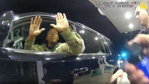 a person in a car: Caron Nazario is seen in this still image from body camera footage holding his hands up before a police officer pepper sprays him.