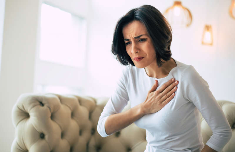 """a woman looking at the camera: According to a 2018 study, """"pill-induced esophagitis is a rare cause of acute chest pain. It is one of the potential side effects of commonly used drugs such as tetracycline, doxycycline, clindamycin, and nonsteroidal anti-inflammatories (NSAIDs). […] Risk factors for the development of drug-induced esophagitis include use of a small quantity of water when swallowing medication, lying down during or immediately after drug ingestion, and the presence of underlying esophageal disorders."""" If you suffer from chest pain, contact your doctor immediately. They might suggest discontinuing the medication and look into underlying conditions."""