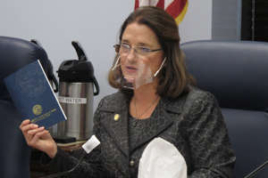 a woman holding a cell phone: FILE — In this Jan. 27, 2021 file photo, Alaska state Sen. Lora Reinbold, an Eagle River Republican, holds a copy of the Alaska Constitution during a committee hearing in Juneau, Alaska. Alaska Airlines has banned the Alaska state senator for refusing to follow mask requirements. Last week Reinbold was recorded in Juneau International Airport arguing with Alaska Airlines staff about mask policies. A video posted to social media appears to show airline staff telling Reinbold her mask must cover her nose and mouth. Reinbold has been a vocal opponent to COVID-19 mitigation measures and has repeatedly objected to Alaska Airlines' mask policy, which was enacted before the federal government's mandate this year. (AP Photo/Becky Bohrer, File)