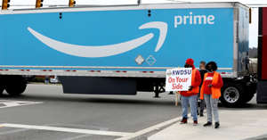 a truck that has a sign on the side of a road: People hold a banner at the Amazon facility as members of a congressional delegation arrive to show their support for workers who will vote on whether to unionize, in Bessemer, Alabama, U.S. March 5, 2021.