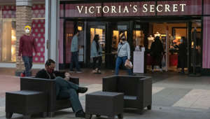 a group of people sitting in front of a store: Shoppers pass in front of a Victoria's Secret store at a mall in San Diego, California, April 22, 2021.