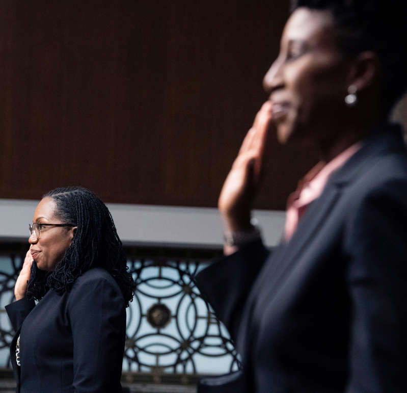 a person talking on a cell phone: Candace Jackson-Akiwumi, nominated to be a U.S. Circuit Judge for the Seventh Circuit, right, and Ketanji Brown Jackson, nominated to be a U.S. Circuit Judge for the District of Columbia Circuit, are sworn in during a Senate Judiciary Committee hearing on pending judicial nominations, Wednesday, April 28, 2021 on Capitol Hill in Washington.