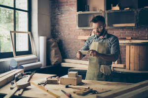 a person cooking in a kitchen: I want to share this photo on social networks! Handsome concentrated bearded with stylish hairdo cabinet maker is taking a picture of his wooden diy using his smartphone