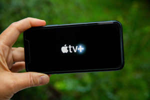 a hand holding a cellphone: Apple TV Plus launched in late 2019 with just nine titles to watch. It's widened its catalog to more than five dozen. Sarah Tew/CNET
