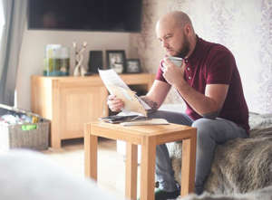 a person sitting at a table using a laptop: Savings account: Saver in pictures