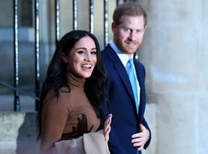Meghan Markle, Prince Harry standing in front of a building: meghan harry