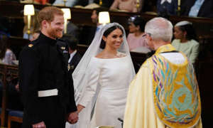 Meghan Markle standing in front of a crowd of people: Harry and Meghan