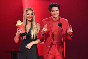a man and a woman standing on a stage posing for the camera: Madelyn Cline and Chase Stokes accept the Best Kiss award for Outer Banks during the 2021 MTV Movie & TV Awards at the Hollywood Palladium on May 16, 2021 in Los Angeles, California.