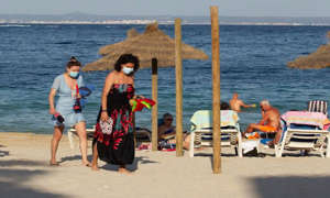 a group of people on a beach near a body of water: Brits can fly to Portugal from Monday 17th May
