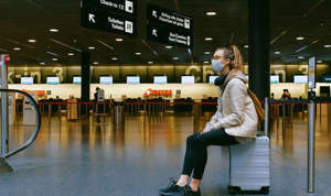 a person waiting at the airport: girl at the airport wearing mask