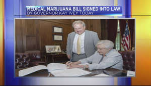 a person sitting in front of a store: Gov. Kay Ivey signs medical marijuana bill into law