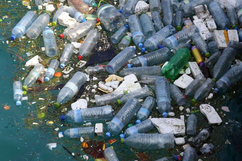 Plastic bottles and polystyrene floating in sea.