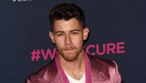 Nick Jonas wearing a pink shirt