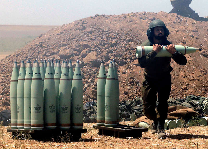 """An Israeli soldiers carries artillery shells during to be fired towards the Gaza Strip, along the border with the Palestinian enclave on May 19, 2021. - Israel is studying whether conditions are right to stop bombing Palestinian militants in Gaza but is preparing for """"more days"""" of strikes if necessary, an Israeli military source said today."""