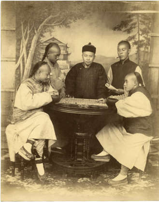 """Slide 8 of 31: This albumen print shows a group of young men playing a board game in Shanghai, around 1880. Once a fishing village, Shanghai was named a treaty port by the British at the end of the First Opium War, in 1842. From then on, as this New York Times/Fodor's feature states, the city was """"carved up into autonomous concessions administered concurrently by the British, French, and Americans, all independent of Chinese law."""" Shanghai grew into a bustling, cosmopolitan trading port attracting not only foreign businesspeople, but migrants from across China."""