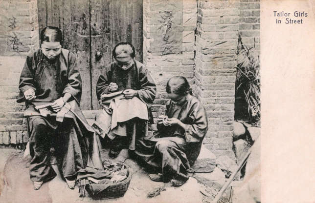 """Slide 30 of 31: This postcard shows young girls sewing clothes at a streetside tailoring workshop in an unspecified Chinese town in the early 1900s. Today, in China as in much of the rest of the world, clothing production has moved away from workshops like this one, into large-scale factories. In 2016, the South China Morning Post reported that tens of thousands of children and young adults, including children under 16, are forced to work long hours sewing clothes, facing docked wages if they """"misbehave."""""""