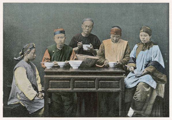 """Slide 15 of 31: This colourized postcard of a family gathered around a table was produced in the 1890s. Chinese cuisine was an object of fascination for the British public at the time, according to researcher R.G. Forman. """"For decades, the exotic and sensuous fare of the Flowery Land had been elaborated for readers back home and from a distance by a multitude of writers and travelers who had tested the cuisine on their behalf,"""" Forman writes. Although some writers emphasized exotic ingredients and """"ritual disgust,"""" others, such as Isabella Bird, raved about the variety of the dishes and the ingenuity of the cooks. """"Cleanly [sic]cooking and wholesome and excellent meals are often produced in dark and unsavoury surroundings,"""" Bird wrote in 1899."""