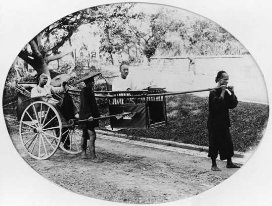 """Slide 4 of 31: This image from the 1870s shows a man being carried on a palanquin (also known as a Chinese sedan chair) by three other people. According to chinaculture.org, use of the palanquin to transport people, usually people of high rank, dates back 4,000 years. """"Generally, the number of carriers and the size of the sedan [chair] can indicate the status of the user,"""" says the site. In centuries past, specially trained civil servants carried high-ranking officials in palanquins; today, when they're used at all, they're used to carry brides on their wedding days."""