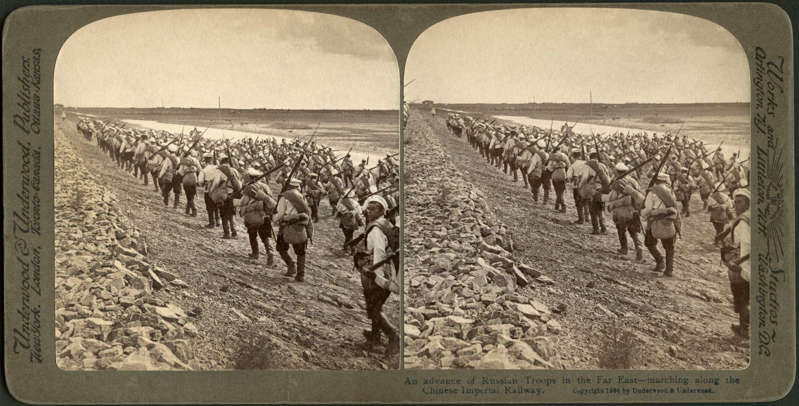 """Slide 27 of 31: This stereo card photo from 1904 shows Russian troops marching along the Chinese Imperial Railway line. The cards, showing two almost-identical photos, are designed to be seen through a stereoscope, a binocular-like device. According to the website Reframing Photography, the stereoscope """"relies upon the principle that each eye sees a slightly different view and that these two dissimilar pictures are united by the brain."""" As a result, """"viewed through the stereoscope, the flat images seem to become one picture with three-dimensional depth."""""""