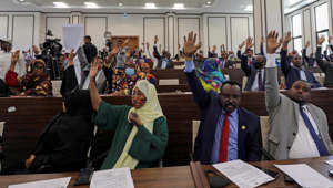 a group of people sitting at a desk: Somalia legislators vote to cancel a divisive two-year presidential term extension, in the lower house of Parliament in Mogadishu, Somalia, May 1, 2021.