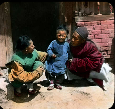 Slide 16 of 31: This family scene from Manchuria, northeastern China, in the early 1900s was colourized and immortalized on a magic lantern slide. As far back as the 17th century, according to the Magic Lantern Society of the United States and Canada, scenes were painted on glass and shown using these early projectors, which work by shining light through glass slides. In the 1850s, the first methods for printing black-and-white photos on glass were developed, although early colour photo slides had to be coloured by hand directly on the glass. Colour transparency film wasn't available until the 1930s.