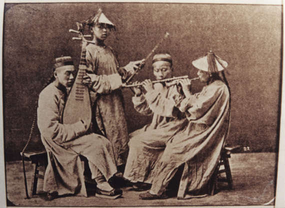 Slide 18 of 31: This postcard from the early 1900s shows a quartet of traditional musicians, including three pipers and one man playing a traditional lute. Chamber music ensembles like this one performed for royalty, for traders and businesspeople, and, in rural areas, for their neighbours, according to Encyclopedia Britannica. Incidentally, the encyclopedia notes that the strings of traditional Chinese instruments aren't made from gut or metal, but from twisted silk.