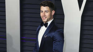 Nick Jonas wearing a suit and tie