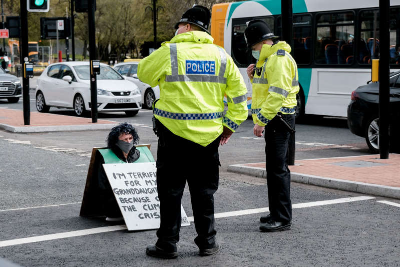 """NEWCASTLE UPON TYNE, ENGLAND - MAY 01: Police speak to an Extinction Rebellion activist sitting in the middle of the road during a """"Rebellion Of One"""" protest on May 01, 2021 in Newcastle upon Tyne, England. Extinction Rebellion is a group of environmental activists who campaign for action to stop the current """"environmental emergency"""". Their tactics are often seen as controversial due to the disruption they cause to the general public. (Photo by Thomas Jackson/Getty Images)"""