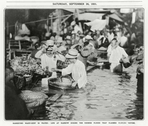 """Slide 5 of 31: This photo from late September 1931 shows traders at an open-air market along the Yangtze River in Wuhan (then Hankow), conducting business while waist-deep in water. According to the History Channel, the Yangtze hit its highest point on August 18, 1931; floods that year killed as many as 3.7 million people, due not only to the rising waters but also to starvation—rice fields were swamped—and epidemics. In normal times, large-scale disaster may have been averted, but """"with much of the area's resources devoted to civil war at the time, the river was neglected."""" The History Channel calls the floods """"perhaps the worst natural disaster of the 20th century."""""""