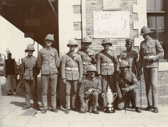 """Slide 10 of 31: This photo from about 1911 shows British soldiers posing with an award, """"possibly in Tientsin (now Tianjin)"""" in northeastern China. The Royal Inniskilling Fusiliers were a regiment from Ireland (then entirely under British control) that arrived in Tientsin in 1909. Until mid-1911, """"duties were light, apart from guards, parades and route marches, with plenty of time for sport."""" The regiment was about to be redeployed to India when they were called back in the context of a mutiny by Chinese troops."""