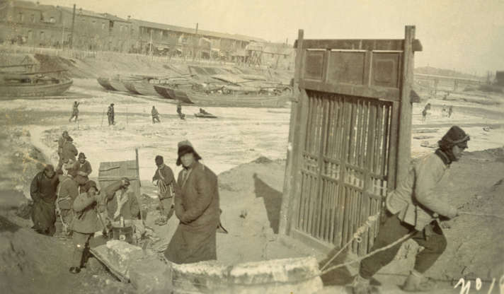 Slide 13 of 31: This picture was taken around 1911 in Tianjin and shows people hauling blocks of ice from a frozen river. Today, as one Scottish expatriate in Tianjin observes, traffic on the city's once-bustling rivers and canals has quieted down, and the banks of the waterways have been largely landscaped into pedestrian-friendly spaces. According to Lonely Planet, when the river freezes over now, instead of hauling the ice away to be melted, some people skate on it.