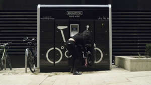 a person standing in front of a window: Brompton reveal their folding bicycle hire service