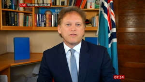 Grant Shapps in a suit standing in front of a book shelf: Holidays: Grant Shapps outlines 'traffic light' system