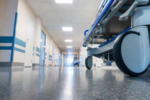 a large room: Medical bed on wheels in the hospital corridor.