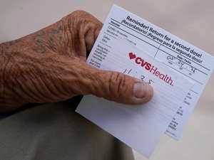 text, letter: A man holding a vaccination reminder card in Miami's Little Havana neighborhood. Not related to this story. Wilfredo Lee/AP